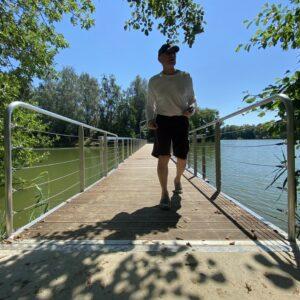 Man walking on pontoon bridge at Lake Pusztaszentlaszlo